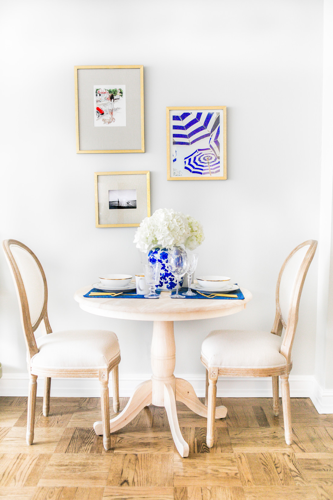 Lauren-Nelson-At-Home-Natural-Wood-Round-Dinning-Table-White-French-Chairs-West-Elm-Gold-Frame-Gallery-Wall
