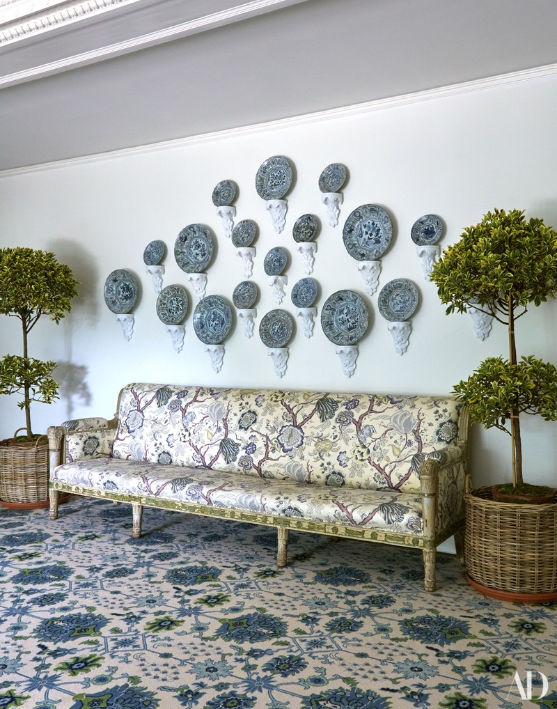 17th-Century porcelain plates salvaged from a shipwreck hangs above an Italian neoclassical sofa. Rug by Patterson Flynn Martin; baskets by Homenature.