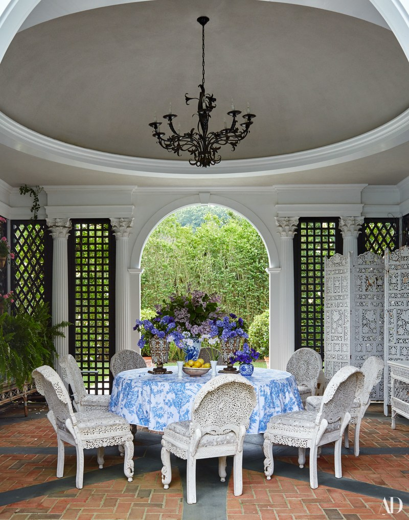 A D. Porthault tablecloth dresses the table in the poolhouse-Vintage chairs by Tony Duquette.