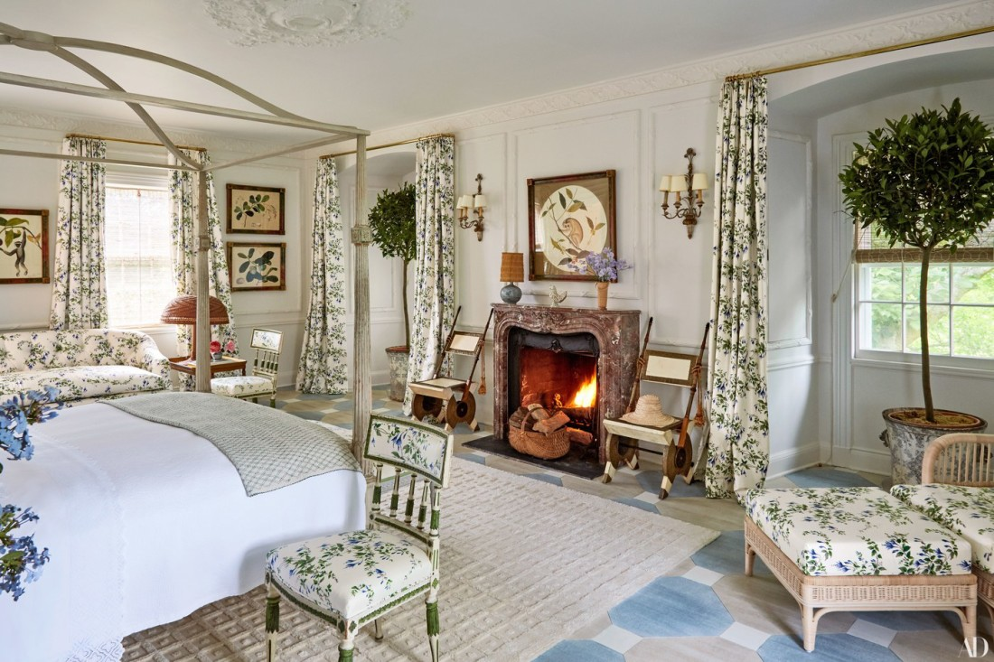 Colefax and Fowler floral master bedroom Tory Burch's Southampton home-painted-George III–style four-poster is dressed in D. Porthault linens-Carlo Bugatti chairs flank the fireplace-botanical prin
